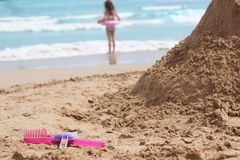 A large sand castle and toy tools on the sand on the beach. Stock Photos