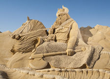 Large sand sculpture of Norse viking. Large sand sculpture statue of an ancient norse viking on horse at sand city theme park against a blue sky background Stock Photography