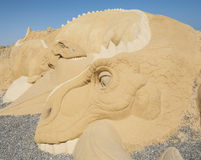 Large sand sculpture statue of a dinosaur. Closeup detail of large sand sculpture statue of a dinosaur at sand city theme park stock image