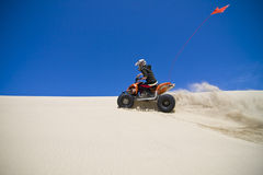 Large sand spray from ATV quadbike rider in the du Royalty Free Stock Photo