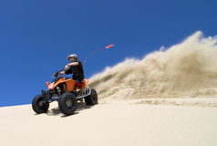 Large sand spray from ATV quadbike rider in the du royalty free stock image