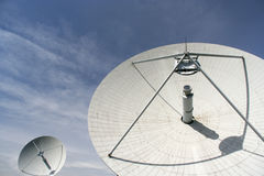 Large satellite dish against lightly cloudy blue s. Two large satellite ground station dishes lit by bright sunlight against blue sky with wispy clouds. Dish Stock Photography