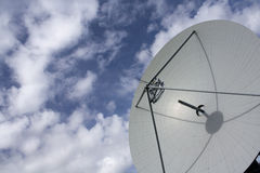 Large satellite dish against lightly cloudy blue s Stock Photo