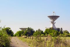 Large satellite dish radar antenna station in green field. Against blue sky. Space Communication Center Stock Images