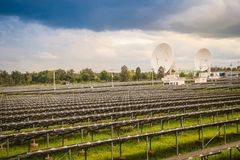 Large scale solar farm with the satellite dishes under dramatic Stock Photography