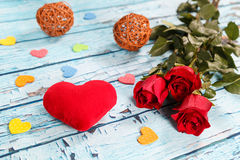 Large scarlet heart and bouquet of red roses on a blue wooden table. Royalty Free Stock Image