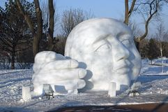 Large sculptured head and hand on a sunny winter afternoon royalty free stock photo