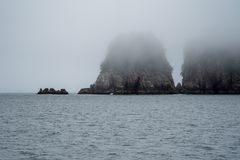 Large sea stacks in Kenai Fjords National Park with a lot of fog in the Resurrection Bay royalty free stock image