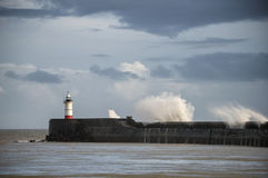 Large sea waves crashing over lighthouse during storm with beaut Royalty Free Stock Photos