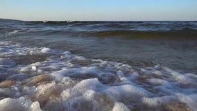 Large sea waves wash shells lying on the sandy beach at sunset on a summer evening. stock footage
