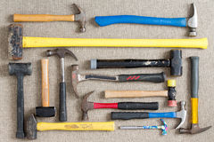 Large selection of different hammers. And mallets arranged on a neutral beige background viewed from above in a DIY, renovation, maintenance,and construction Stock Image