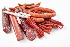 Large selection of dried spicy seasoned sausages. Large selection of different dried spicy seasoned beef and pork sausages on a white background for advertising Stock Images