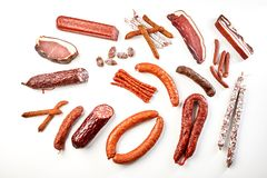 Large selection of spicy sausages in a flat lay. Large selection of spicy cured, smoked and dried sausages, ham, kassler, and bacon in a flat lay arrangement stock images