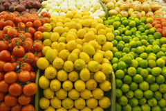 Large selection of tomatoes, lemons and limes on display in market, close-up (full frame) Royalty Free Stock Photos