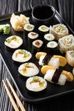 Large set of Japanese rolls such as Hosomaki, Uramaki, Maki, Nigiri, Tamagoyaki served with ginger, wasabi and soy sauce close-up. On a plate on the table stock image