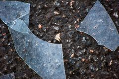 Large shards of glass on top of the asphalt. Large shards of glass on the asphalt royalty free stock photos