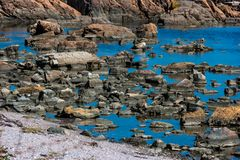 Large sharp stones in the water. Stony sea shore. Background Royalty Free Stock Photos