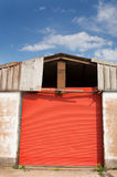 Large shed with red door. Large old shed with red metal door, photographed against a blue sky Stock Photos