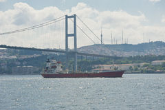 Large ship under a suspension bridge on river Royalty Free Stock Photo
