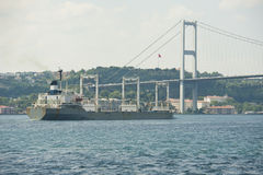 Large ship under a suspension bridge on river Stock Photo