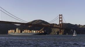 Large shipping boat run under Golden Gate Bridge royalty free stock images