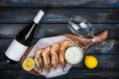 Large shrimp or langoustine with white sauce, bottle of wine, glass for the wine and half of a lemon on a wooden board. Top view Stock Image