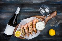 Large shrimp or langoustine with white sauce, bottle of wine, glass for the wine and half of a lemon on a wooden board royalty free stock photos