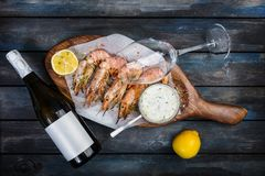 Large shrimp or langoustine with white sauce, bottle of wine, glass for the wine and half a lemon on a wooden board. Top. View Stock Image