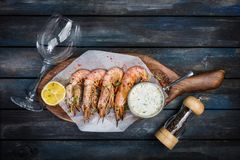 Large shrimp or langoustine with white sauce pepper-pot glass for the wine and half a lemon on a wooden board. Top view.  Royalty Free Stock Images