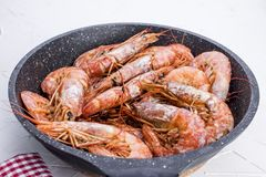 Large shrimps fried in a frying pan. On a white table. Lunch from seafood. Free space for text. Copy space stock photography