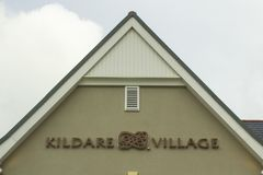 A large sign on a gable wall at the entrance to the prestigious Kildare Village retail park in County Kildare Ireland. 15 March 2018 A large sign on a gable wall royalty free stock image