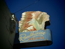 Roadhouse Relics Sign in Austin Texas. A large sign with a Native American man in a headdress and the words `Roadhouse Relics` taken during the day under blue stock photos