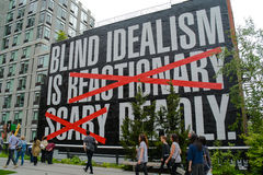 Large sign on side of building on High Line in New York City. Tourists and locals walk past sign with text: blind idealism is reactionary scary deadly, with Royalty Free Stock Photos