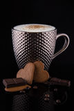 Large silver mug of coffee with reflective pimples and gingerbiscuits chocolate and beans. On the reflective black table royalty free stock images