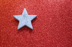 Large silver star on red background glowing bright Stock Photos