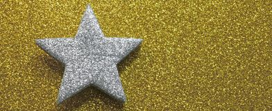 Large silver star sparkling in brilliant golden background Stock Photos