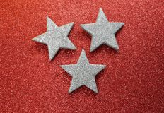 Large silver stars on bright red glittery background Stock Image