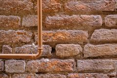 Ancient stone wall and copper pipe. Large size close up photo of an old brick wall. You may see almost colorless light beige stone wall made of sandstone bricks stock photos