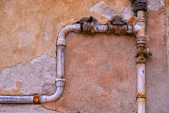 Ancient stone wall and metal water pipes. Large size close up photo of an old stone wall and old metal water pipes. You may see almost colorless light beige royalty free stock photo