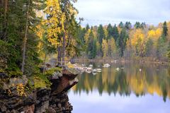 Forest, lake, fresh air and rocks. Large size good quality photo of a forest, wonderful hilly lake view, autumn trees mirroring in the water, some huge rocks Royalty Free Stock Photos