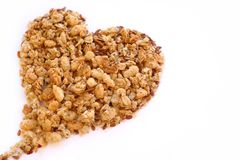 Cereals, muesli, life, white. Large size photo of a heart made of various cereals and muesli: you may see closely different seeds, cereals, dried berries, etc Stock Image