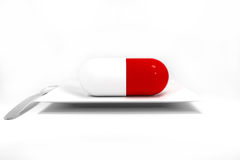Large sized red pill on white plate Stock Photos