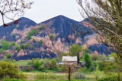 The large slag heap and small village among flowering spring trees royalty free stock images