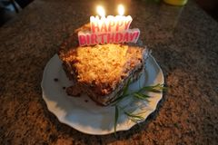 Large slice of German chocolate cake. A large slice of German Chocolate cake lit with candles saying `Happy Birthday stock photos