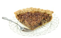 Large Slice of Pecan Pie. A large slice of homemade pecan pie on a crystal plate with a fork, isolated on white background, horizontal with copy space Royalty Free Stock Image