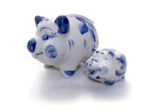 Large and small ceramic pigs. Details of a large and small, porcelain or ceramic pigs with blue highlights.  White background Stock Image