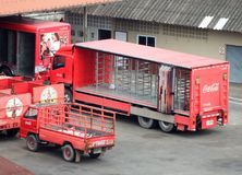 Large and small Coca-Cola branded delivery trucks await loading at a depot. Rayong, Thailand - January 27th, 2018: Variety of branded trucks parked up at a Coca Stock Image