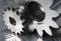 Large and small mechanical part. Small and large gears, cogs connecting against patternd steel royalty free stock photography