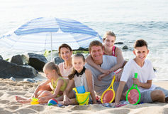 Large smiling family of six people together on beach Stock Photography