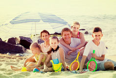 Large smiling family of six people together on beach royalty free stock image